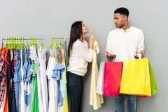 Lady begging clothes from confused man holding shopping bags. Stock Images