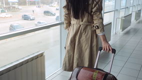 Lady in beige coat with black hair carries suitcase. Her luggage is made from crocodile skin and painted in brown color. Woman walks on white tile floor and stock video