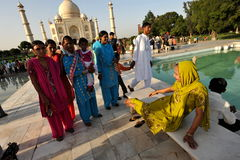 Lady being photographed near Taj Mahal. Family taking photo of their sister in front of the mausoleum of Taj Mahal Royalty Free Stock Photo