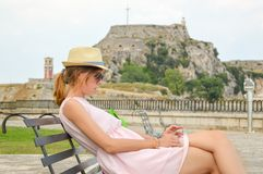 Lady on the bench with an old fortress in background. Lady sitting on the bench with an old fortress in background Stock Photography