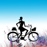 Lady on bicycle in grass. The outline or silhouette of a woman with a bicycle on a graduated blue to white background with a three dimensional border  of tall Stock Photos