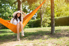 Lady with big hat sitting in hammock Royalty Free Stock Image