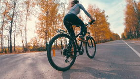 Lady on the bike. Lady riding a bicycle on the asphalt road with trees during autumn stock footage