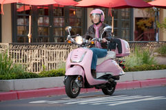 Lady biker on pink scooter. Youthful sixty year old biker riding on a city street Stock Photo