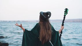 Lady with black big horns on head in long green dress with golden belt with magic band in hand near river, witch with