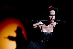 Lady in black carries whip Royalty Free Stock Photography