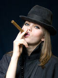 Lady in black and a cigar. Graceful lady in a hat and a cigarette in a hand Royalty Free Stock Image