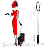 Lady with black dog. Walking lady in red with small black dog Royalty Free Stock Photos