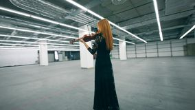 A lady in a black dress is playing the violin with enthusiasm. 4K stock footage