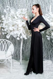 Lady in black dress in a snow covered park royalty free stock image