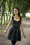 Lady in black dress in summer park Royalty Free Stock Image