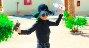 The Lady with the Black hat Laughing and having fun under the sun. The Lady in black with the Black hat having fun under the sun in the garden Royalty Free Stock Photography