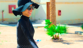 The Lady with the Black hat Laughing and having fun under the sun. The Lady in black with the Black hat having fun under the sun in the garden Royalty Free Stock Photo