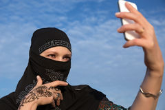 Lady in Black Hijab Holding Telephone. Smiling Arabic Woman Dressed in Traditional Islamic Clothing with Hidden Face Doing Self Portrait with White Smart Phone Royalty Free Stock Photography