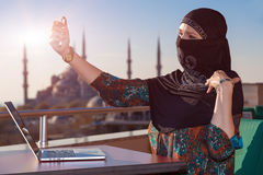 Lady in Black Hijab Holding Telephone. Smiling Arabic Woman Dressed in Traditional Islamic Clothing with Hidden Face Doing Self Portrait with White Smart Phone Royalty Free Stock Images