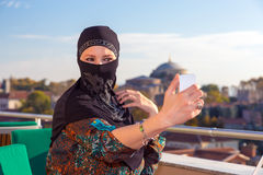 Lady in Black Hijab Holding Telephone. Smiling Arabic Woman Dressed in Traditional Islamic Clothing Hidden Face Doing Self Portrait with White Smart Phone Blue Stock Image
