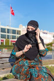 Lady in Black Hijab Holding Telephone and talking. Smiling Arabic Woman Dressed in Traditional Islamic Clothing with Hidden Face talking White Smart Phone Blue Royalty Free Stock Image