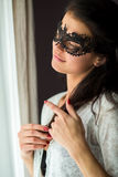 Lady in black lace mask. Woman touching her hair. Dreaming about love Royalty Free Stock Images