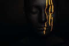 Lady in black paint with yellow smudges. Close-up dark portrait of woman in black paint with yellow smudges isolated on black Royalty Free Stock Image