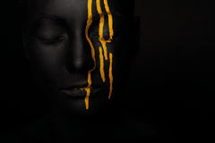 Lady in black paint with yellow smudges. Close-up dark portrait of woman in black paint with yellow smudges isolated on black Stock Photos
