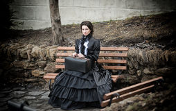 Lady in black sitting on a bench Royalty Free Stock Image