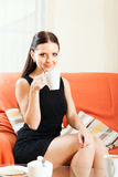 Lady in black on  sofa with  mug Stock Photos