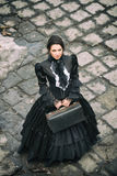 Lady in black standing on a cobblestone pavement. Royalty Free Stock Photos