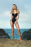 Lady in black swimsuit on seashore Stock Photo