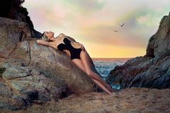 Lady in black swimsuit on seashore. Beautiful lady in black swimsuit on rocky shore. Sunset travel photo Royalty Free Stock Photo