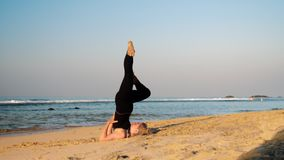 Lady in black tracksuit keeps ballnce with raised legs. Lady in black tracksuit keeps balance with raised legs on sand beach in yoga pose Rejuvenation near ocean stock video