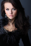 Lady In A Black Velvet Dress. The beautiful girl with wavy hair in a black velvet dress with feathers Stock Photography
