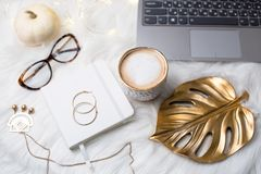 Lady bloggers white work space with gold details, laptop and cof royalty free stock photos
