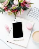 Lady bloggers work desk with pink flowers and macaron cakes on w. Hite table background, feminine home office workspce with coffee and smartphone mock-up royalty free stock photography