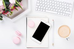 Lady bloggers work desk with pink flowers and macaron cakes on w. Hite table background, feminine home office workspce with coffee and smartphone mock-up royalty free stock images