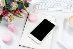 Lady bloggers work desk with pink flowers and macaron cakes on w. Hite table background, feminine home office workspce with coffee and smartphone mock-up stock photos