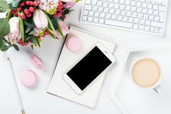 Lady bloggers work desk with pink flowers and macaron cakes on w. Hite table background, feminine home office workspce with coffee and smartphone mock-up royalty free stock photos