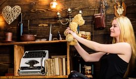 Lady blonde enjoy leisure with teddy bear. Rest and relax concept. Girl in black clothes holds teddy bear toy in hand. Wooden interior on background. Woman on stock image