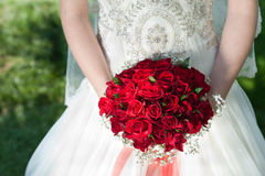 Lady with blood red roses bouquet. Bride lady with blood red roses Royalty Free Stock Image