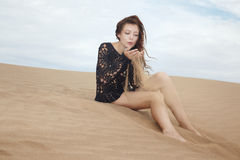 Lady blowing on sand grains Stock Photos