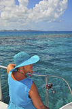 Lady in Blue on the Boat. Middle-aged woman in a blue hat and blue dress on a sailboat in the ocean Royalty Free Stock Images