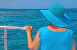 Lady in Blue on a Boat. A middle-aged woman in a blue dress and a blue hat views the sea from a boat Royalty Free Stock Images