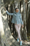 Lady in blue jacket and pink pants standing next to the trees Stock Image