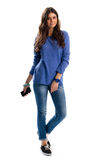 Lady in blue pullover. Young woman holds phone. Sports watch of blue color. Spring outfit with fabric shoes Royalty Free Stock Photo