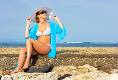 Lady in blue shawl on the beach. Brunette lady with white hat sitting on the rocky beach Royalty Free Stock Images
