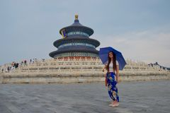 Lady with blue trousers and blue umbrella in front of Blue Temple of Heaven, China stock photo