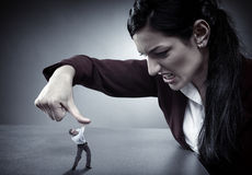 Lady boss crushing her employee. Lady boss crushing an employee under her thumb like a bug Royalty Free Stock Images
