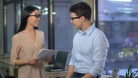 Lady boss pleased with material prepared by male journalist, success at work. Stock footage stock video