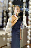 Lady in the boutique. Beautiful buyer with fawny bag in the boutique Royalty Free Stock Photo
