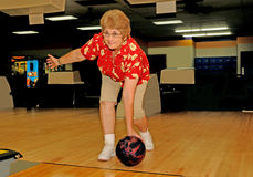 Lady Bowling. Front view of woman bowler releasing ball at the fowl line Royalty Free Stock Photo