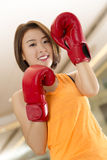 Lady boxer. An Asian lady in boxing pose in a gym Stock Photos